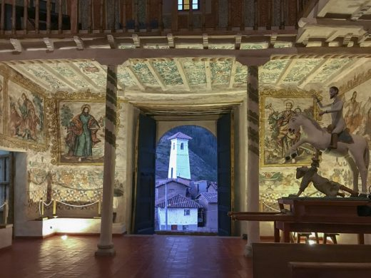Interior view of the wall paintings and statue of Saint Santiago, patron saint of the church of Kuñotambo with the bell tower